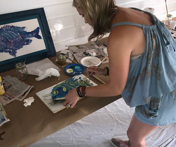Woman paints a fish on a canvas
